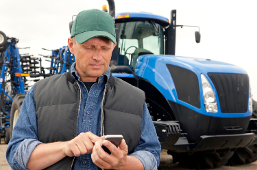 farmer using phone near tractor