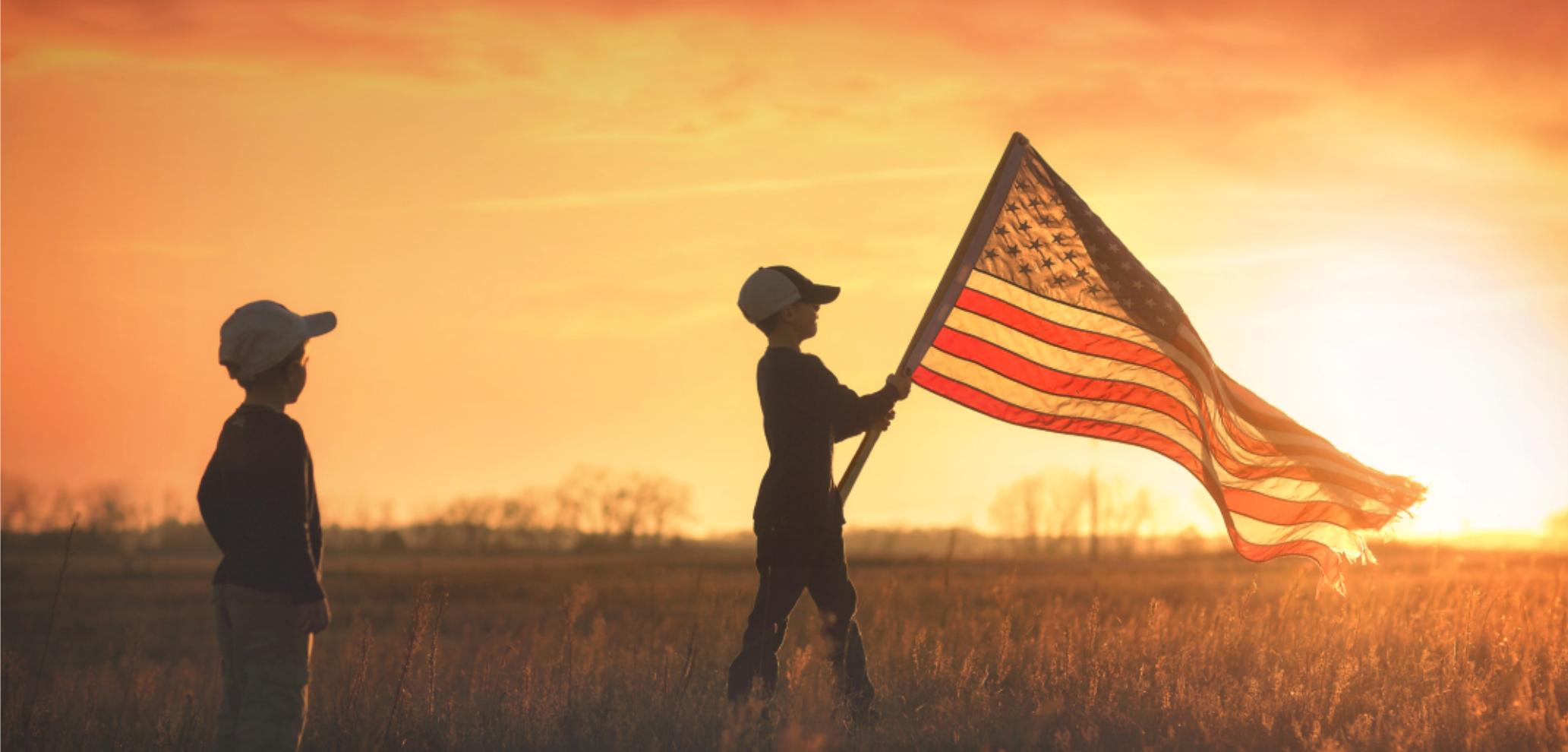 young boys and american flag at sunset